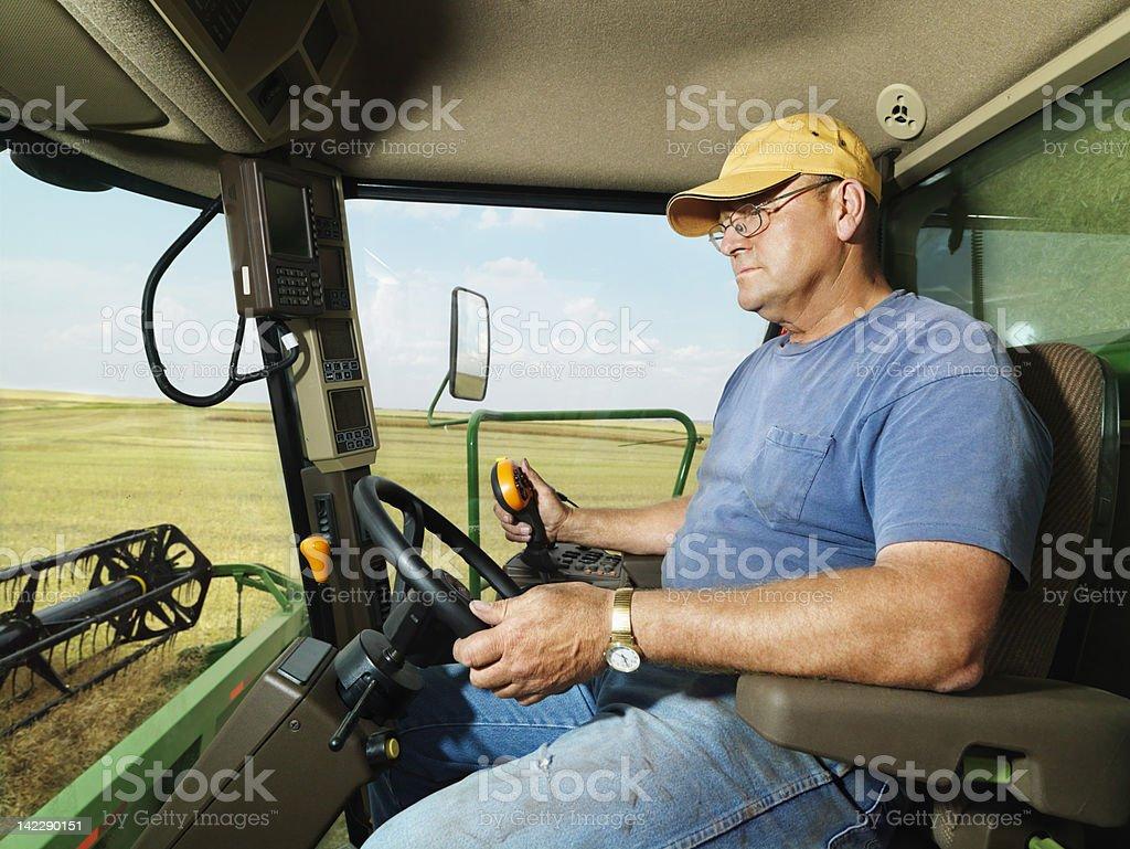 Farmer in combine harvesting crop. royalty-free stock photo