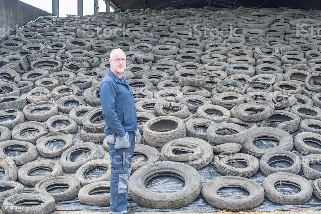 Farmer in shed of silage covered in old tyres stock photo