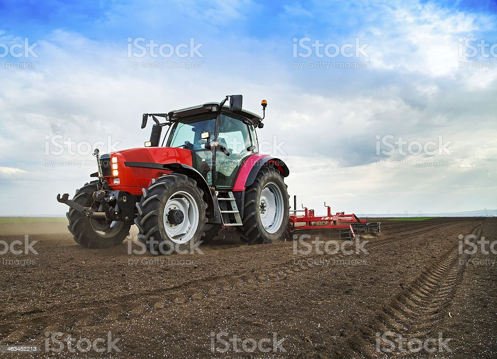 Farmer in tractor preparing land for sowing stock photo
