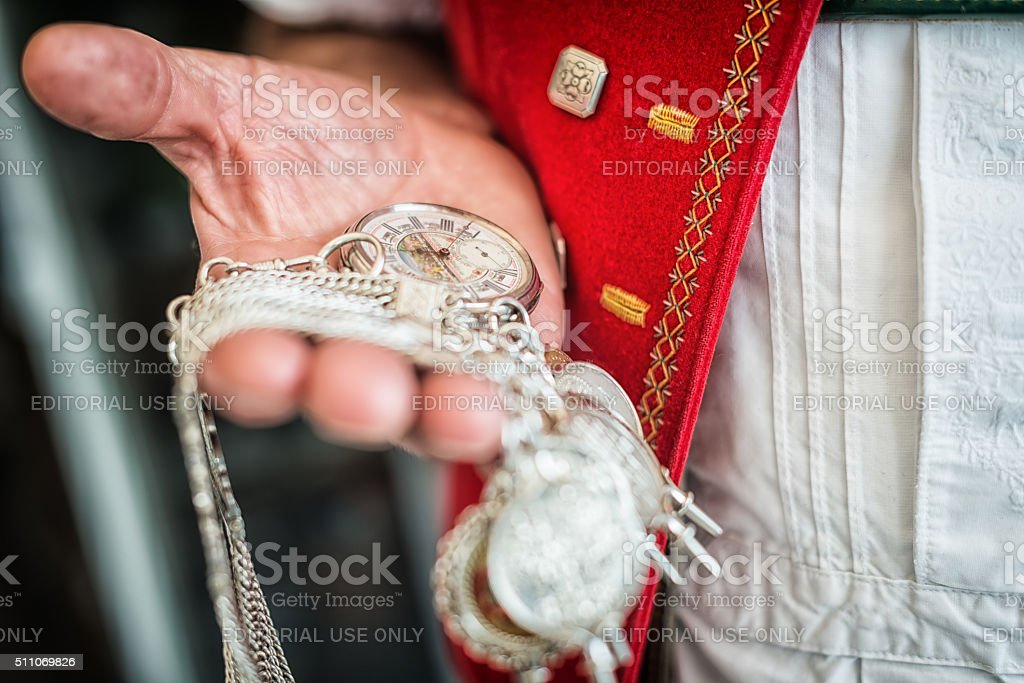 farmer in traditional swiss costume checks time on pocket watch stock photo