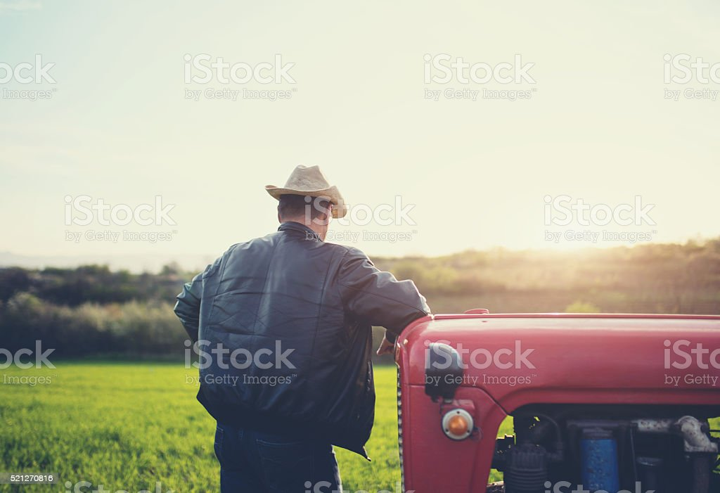 Farmer leaning on tractor stock photo