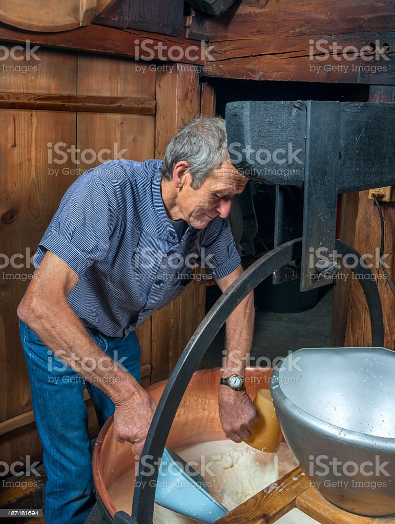 farmer making traditional Swiss cheese in the Alps stock photo