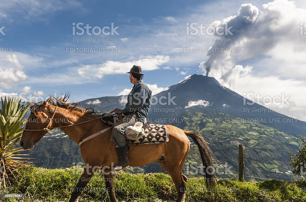 Farmer on a horse looking at the Tungurahua eruption stock photo