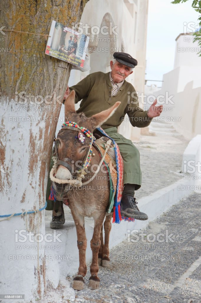 Farmer on donkey waiting for tourists to take a picture royalty-free stock photo