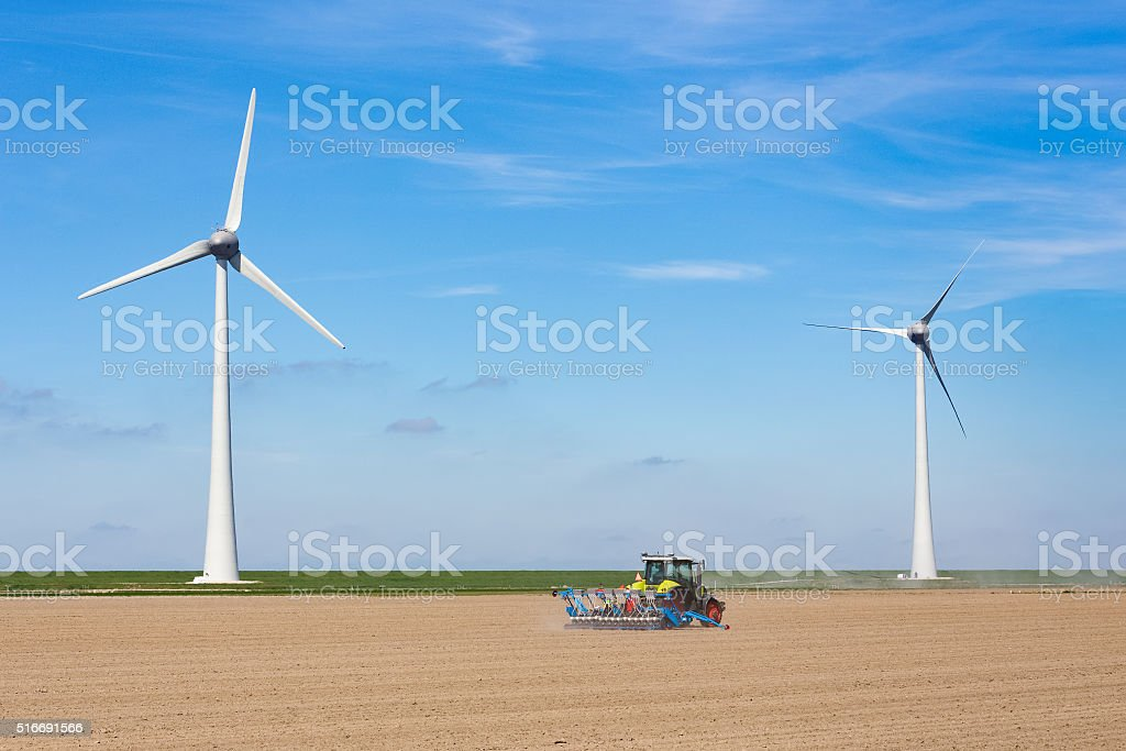 Farmer on tractor sowing in soil near dike and windmills stock photo