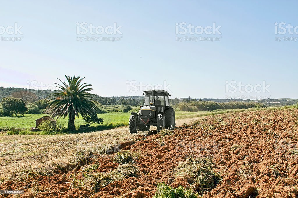Farmer ploughing land with the tractor royalty-free stock photo