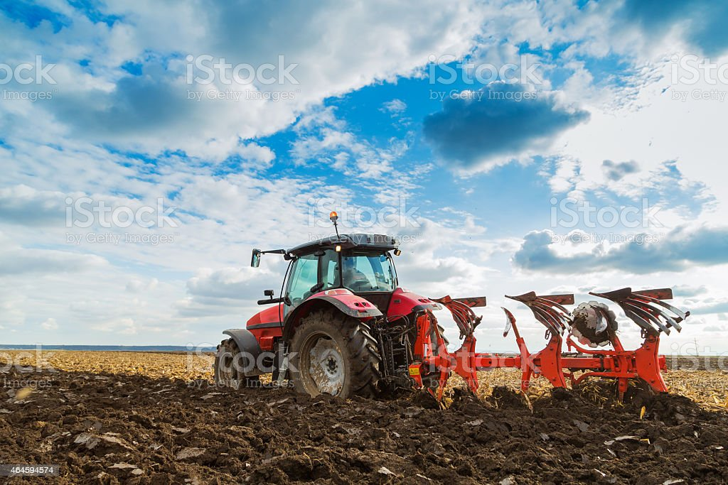 Farmer plowing field in red riding tractor stock photo