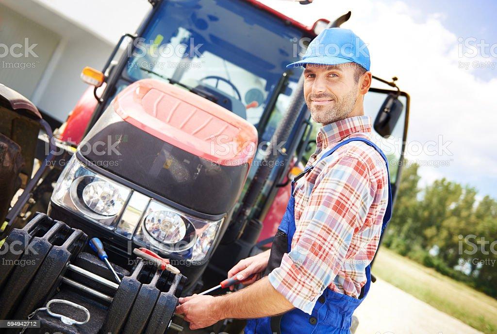 Farmer repairing his big tractor stock photo