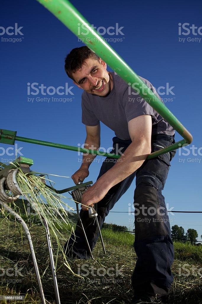 farmer repairing his hay raker, looking at camera stock photo