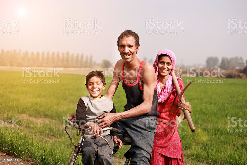 Farmer riding cycle to the field with his family stock photo