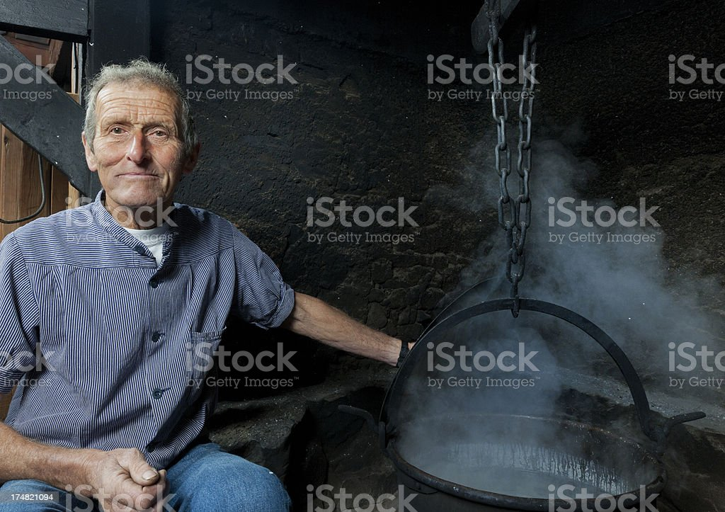 farmer sitting next to log fire and boiling kettle royalty-free stock photo