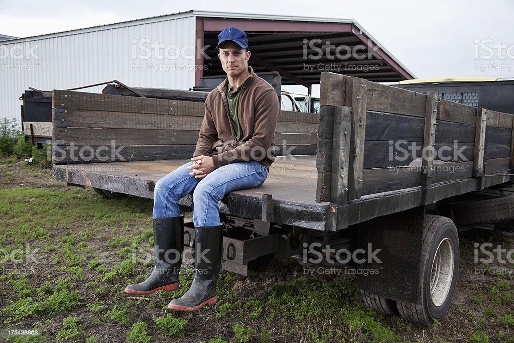 Farmer sitting on back of truck stock photo