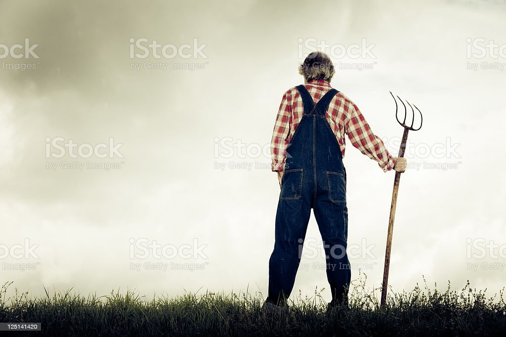farmer standing at the top of a hill stock photo