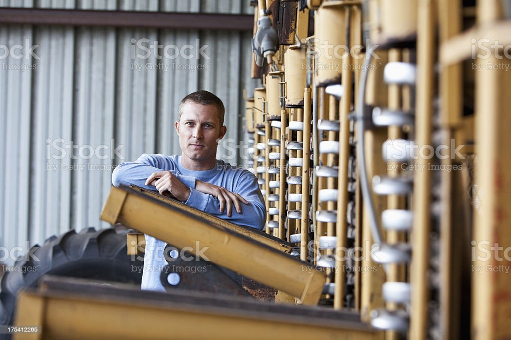Farmer standing next to potato harvester royalty-free stock photo