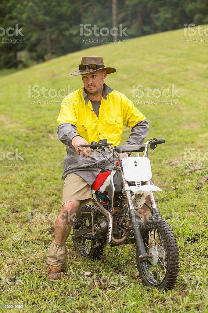 Farmer Trail Bike Riding Through a Paddock on a Farm stock photo