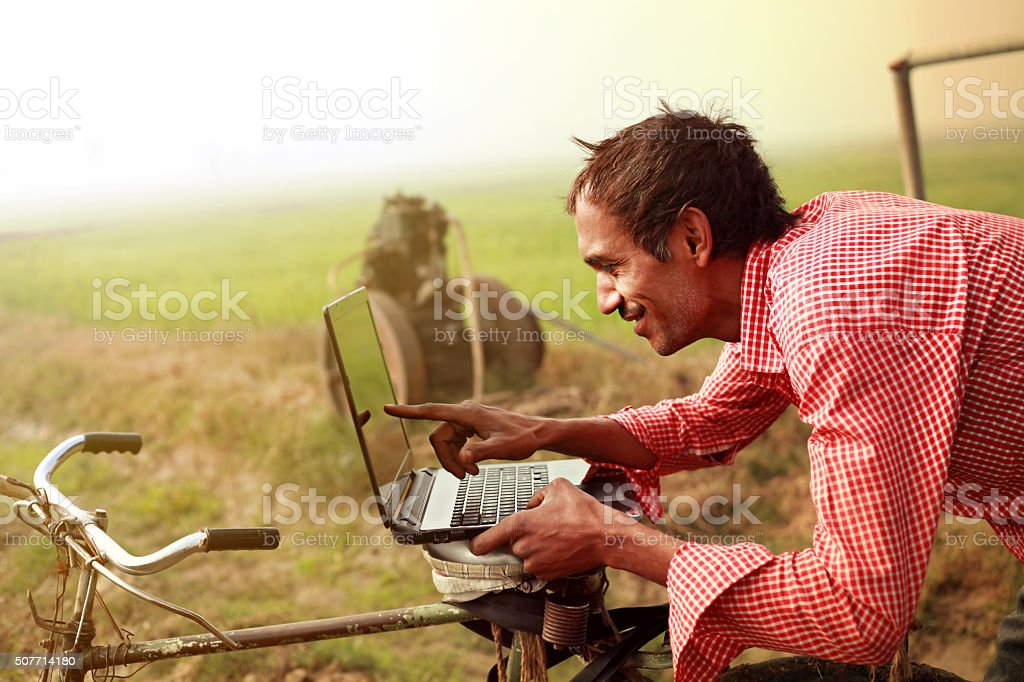 Farmer using laptop in the field stock photo