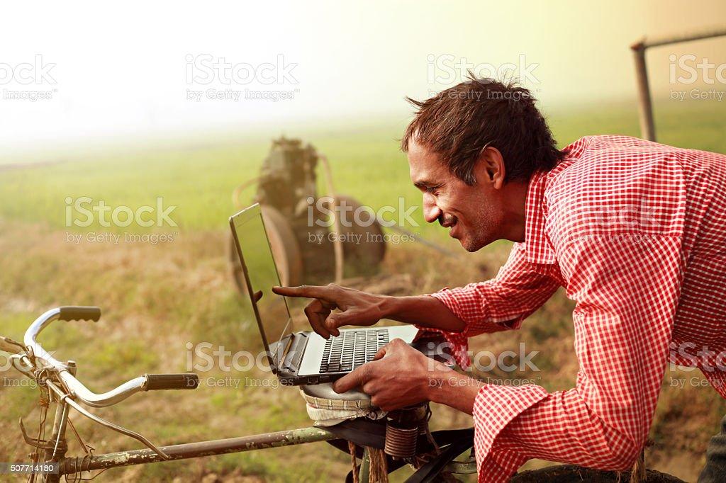 Farmer using laptop in the field stock photo