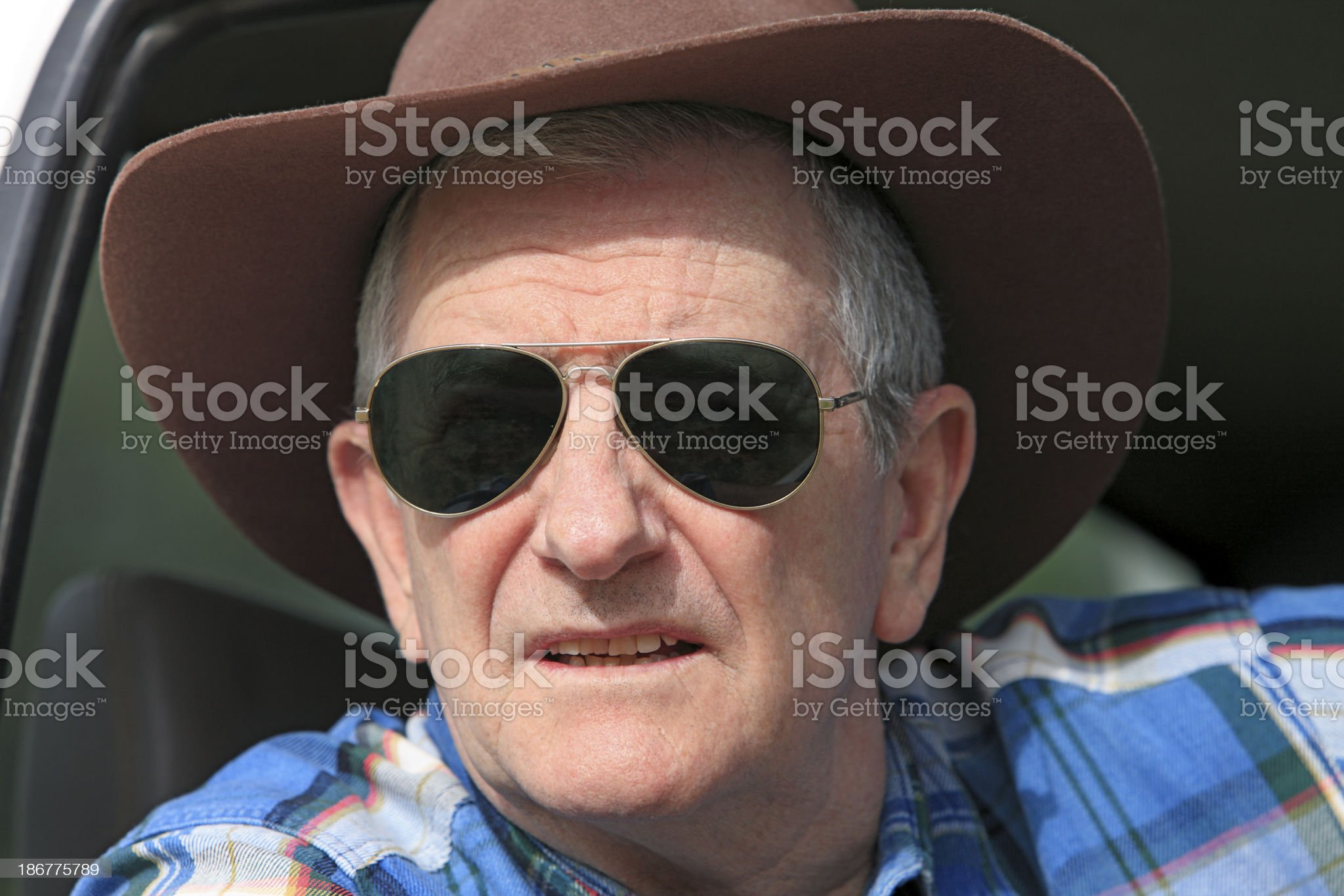 Farmer wearing sunglasses looking out of vehicle royalty-free stock photo