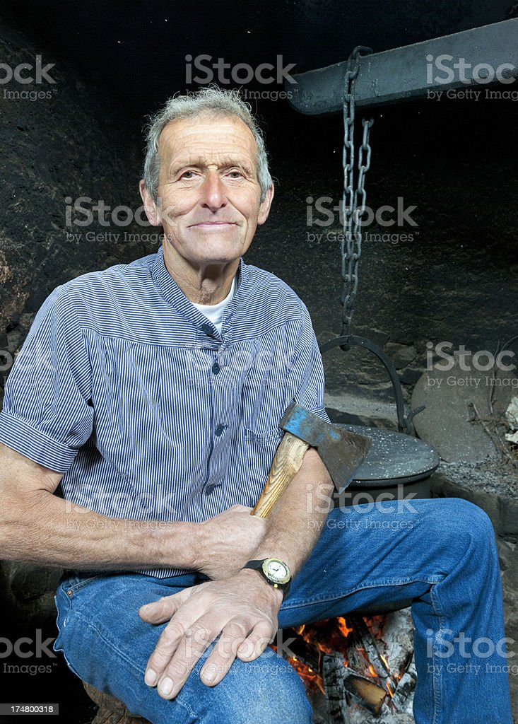 farmer with axe sitting next to log fire in farmhouse royalty-free stock photo