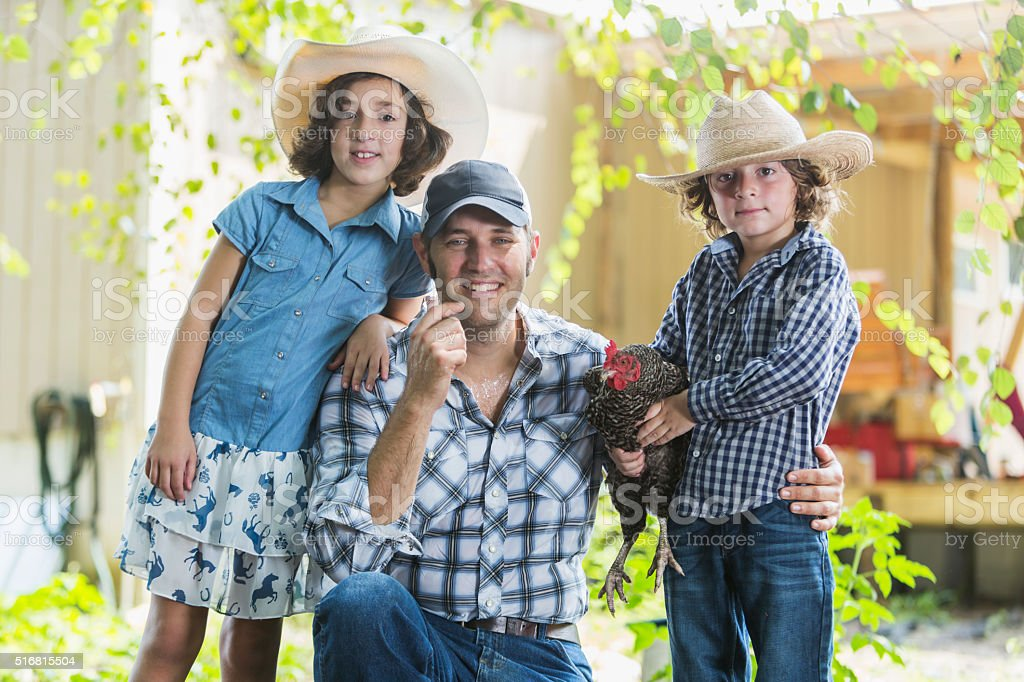 Farmer with children on family farm holding chicken stock photo