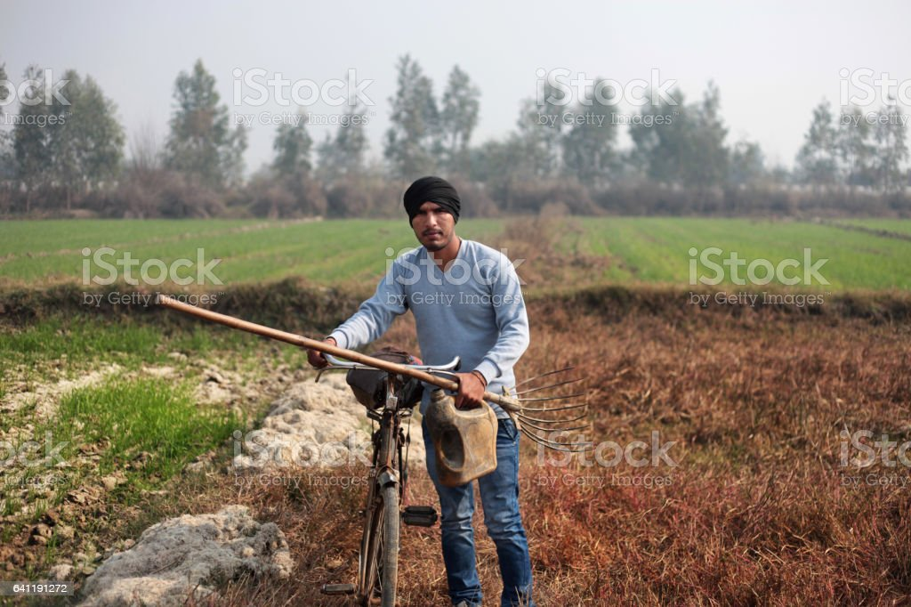 Farmer with fork and bicycle in the field stock photo