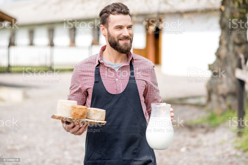 Farmer with milk and cheese outdoors stock photo