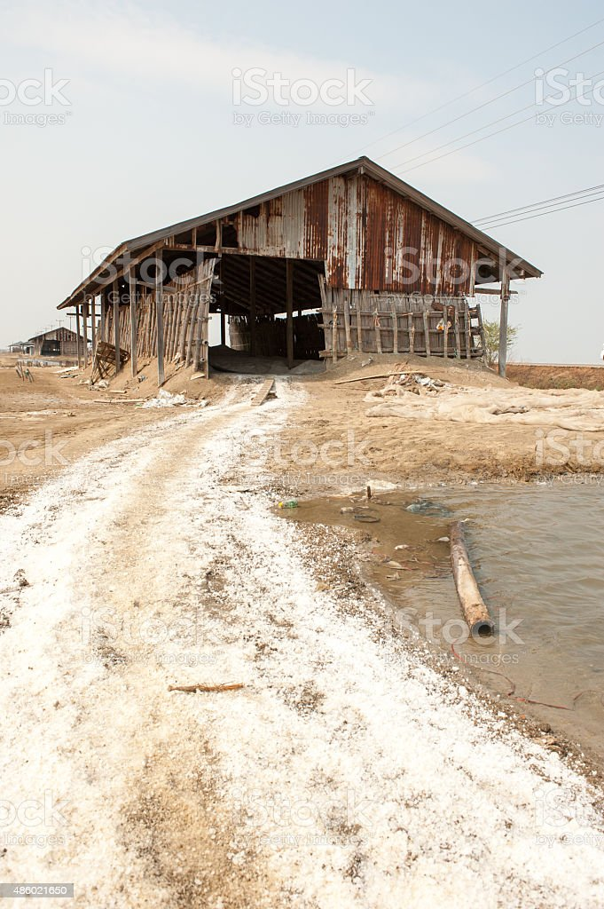 Farmer working at Salt pile in Thailand stock photo