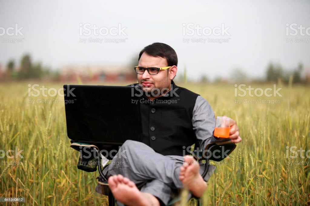 Farmer working on the laptop in the nature stock photo
