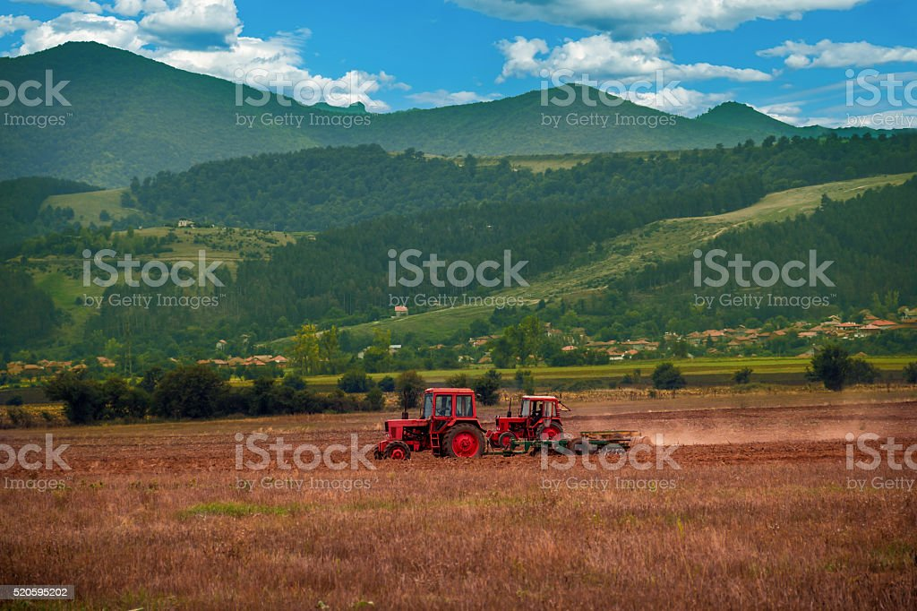 farmer working the fields with tractor and plow stock photo
