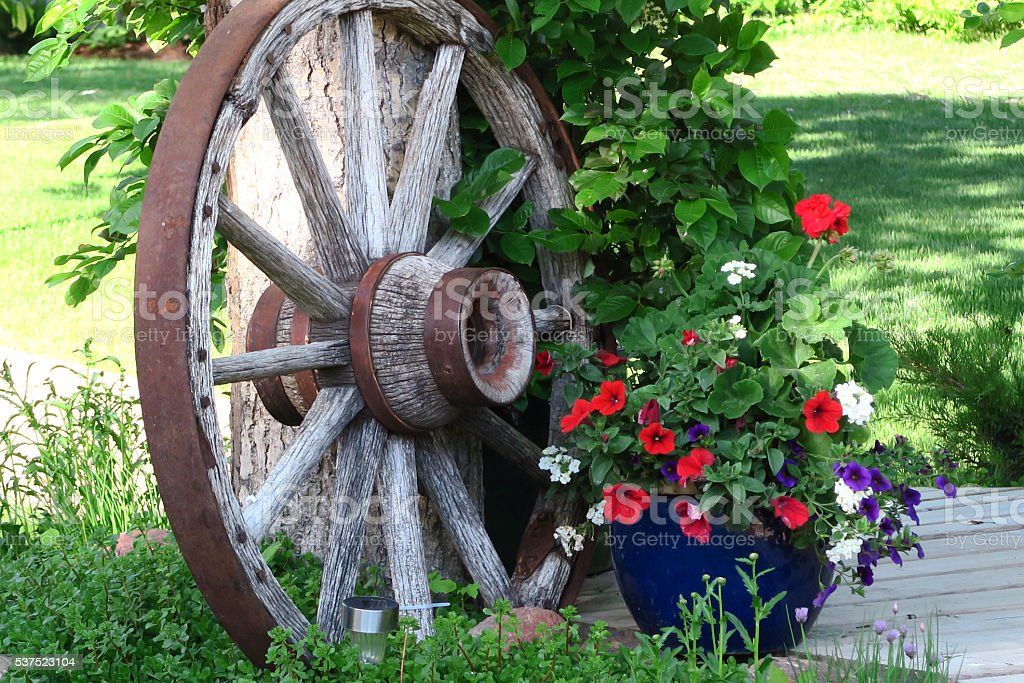 Farmer's antique wagon wheel with pots of flowers stock photo