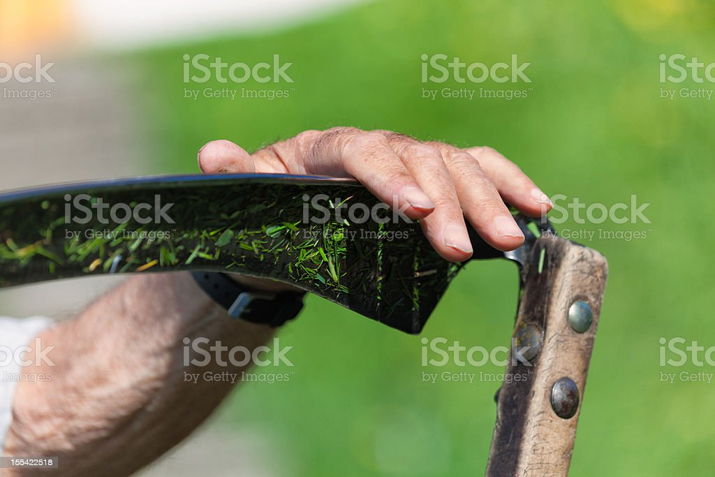 Farmer's hand holding a scythe, mowing Swiss Alps stock photo