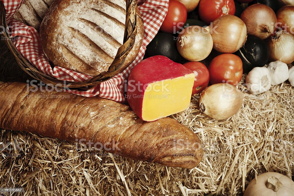 Farmers' Market fare: rustic bread, cheese and vegetables on straw royalty-free stock photo
