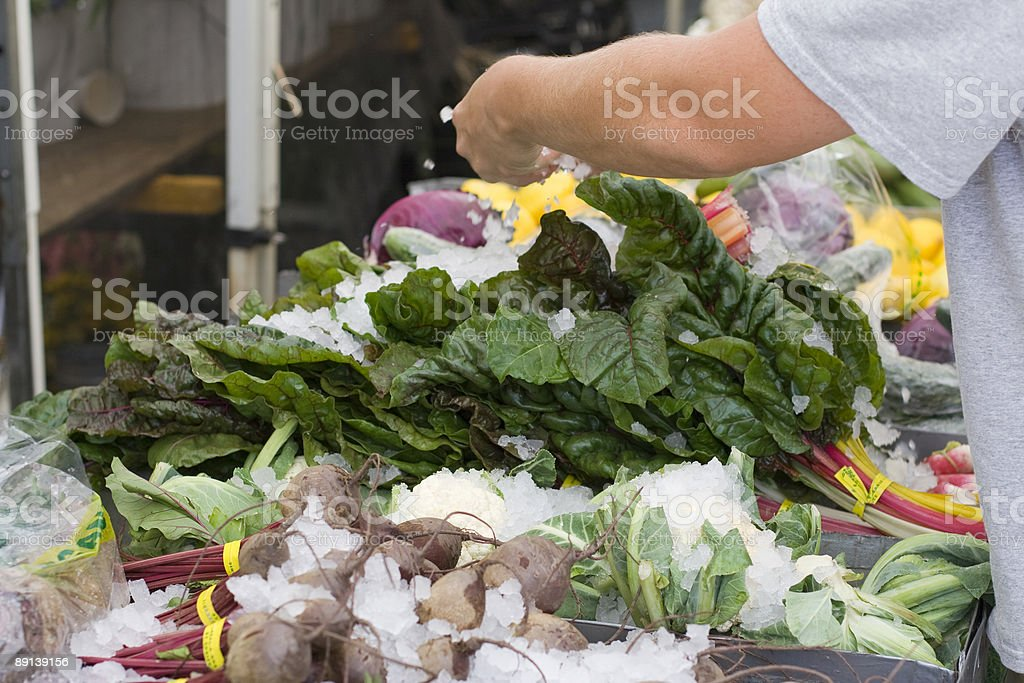 Farmers market worker spreads ice on organic vegetables royalty-free stock photo