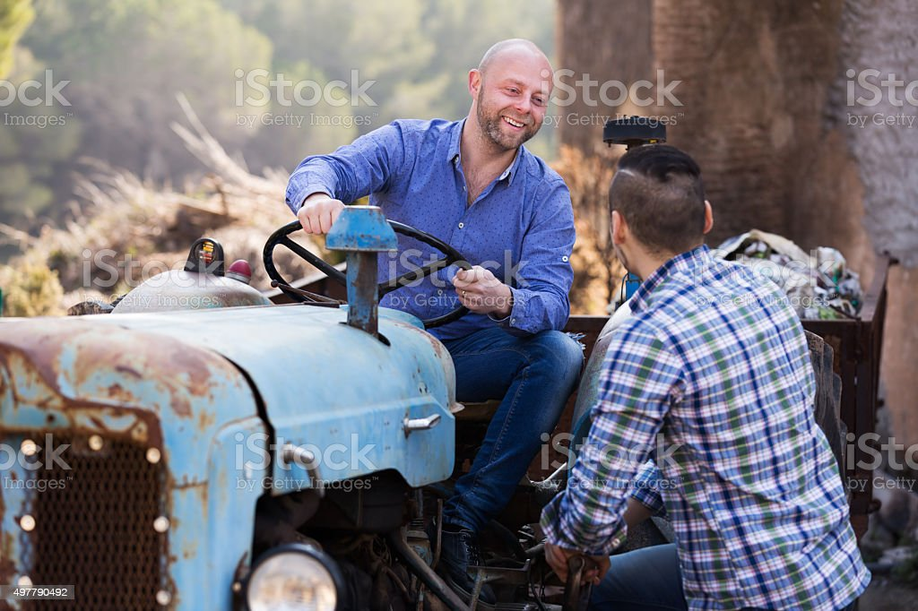 Farmers near agricultural machinery stock photo