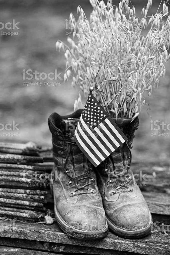 Farmer's Old Leather Work Boots with Flag and Oats stock photo
