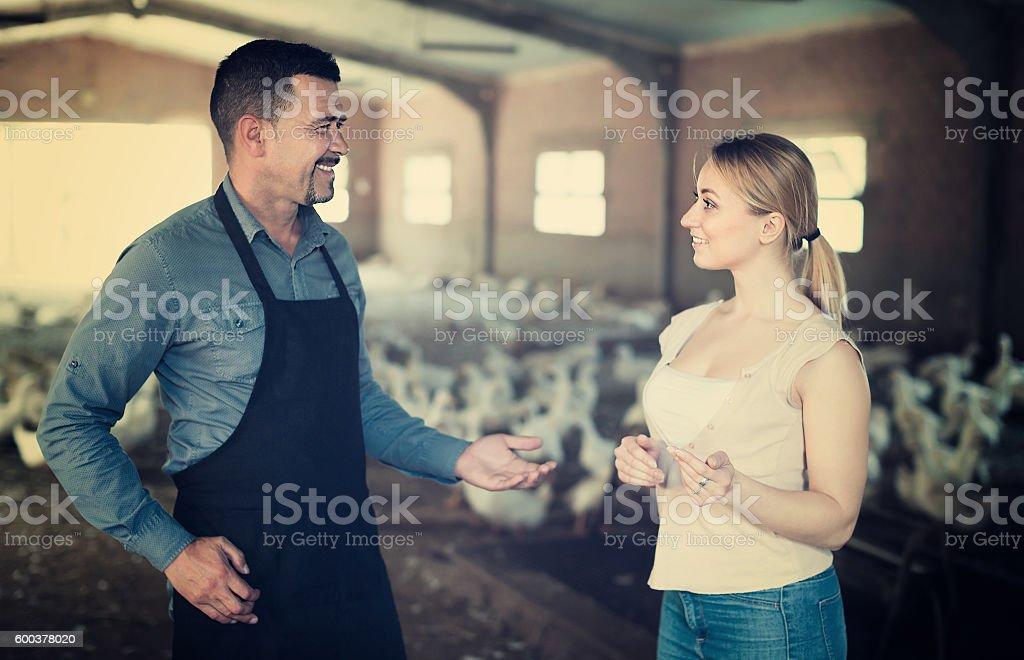 Farmers talking in hangar with ducks stock photo