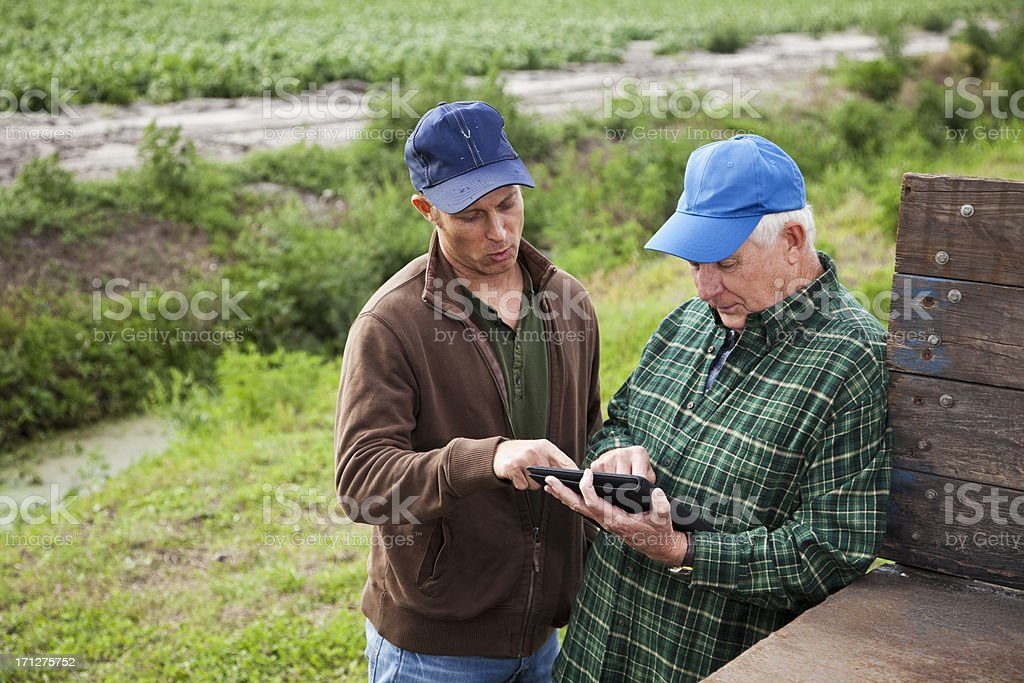 Farmers using digital tablet on potato farm royalty-free stock photo