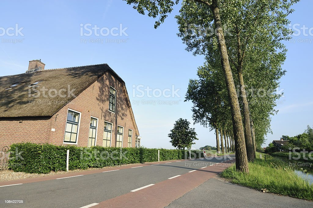 Farmhouse along a road with trees in the Netherlands royalty-free stock photo