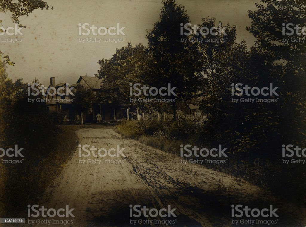 Farmhouse at End of Rural Dirt Road, Vintage Style Photograph stock photo