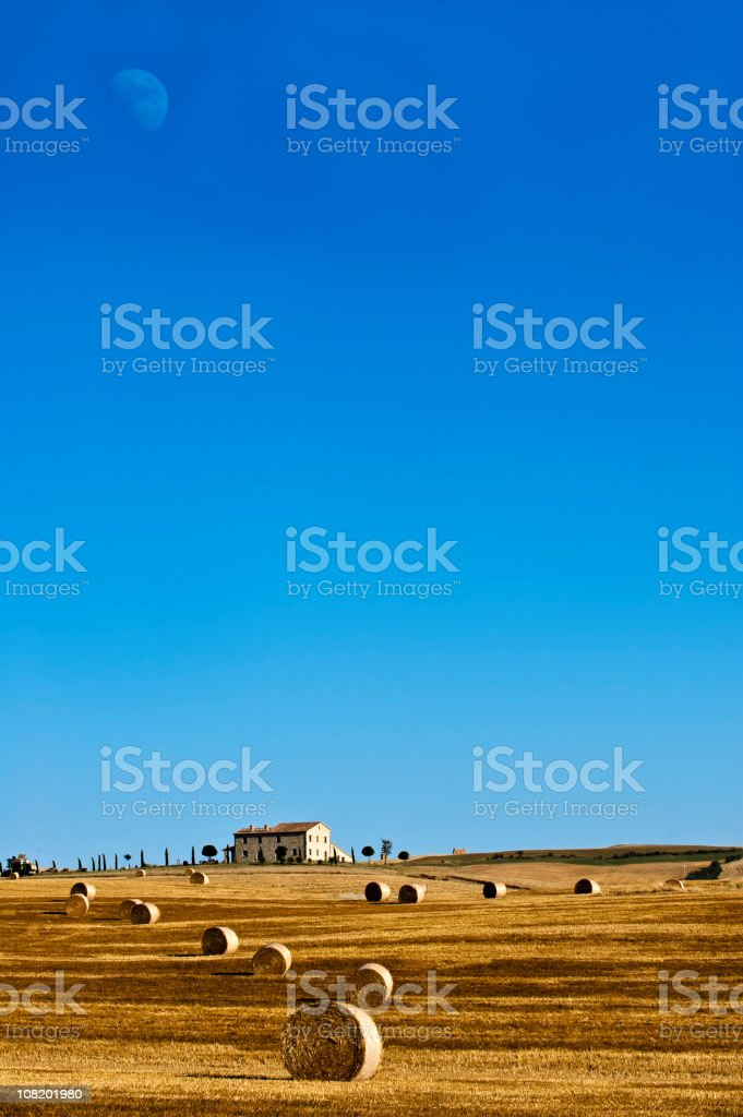Farmhouse in Field with Moon. Blue Sky. Color Image royalty-free stock photo