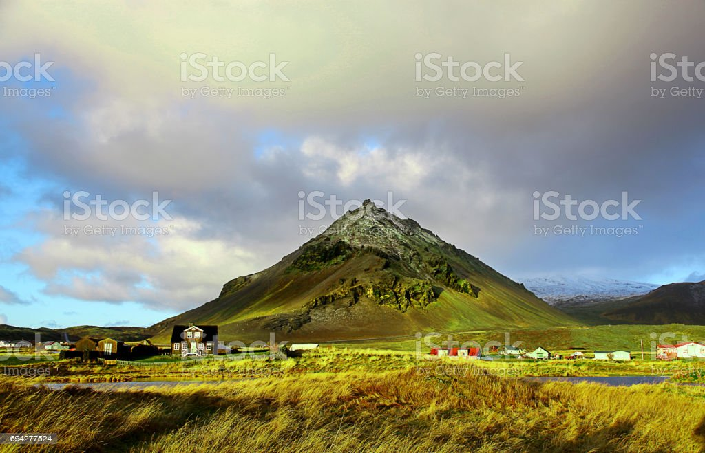 Farmhouse in front of dramatic mountain in Arnarstapi Iceland stock photo