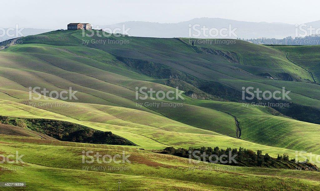 Farmhouse on hill in landscape of Crete Senesi, Tuscany, Italy royalty-free stock photo