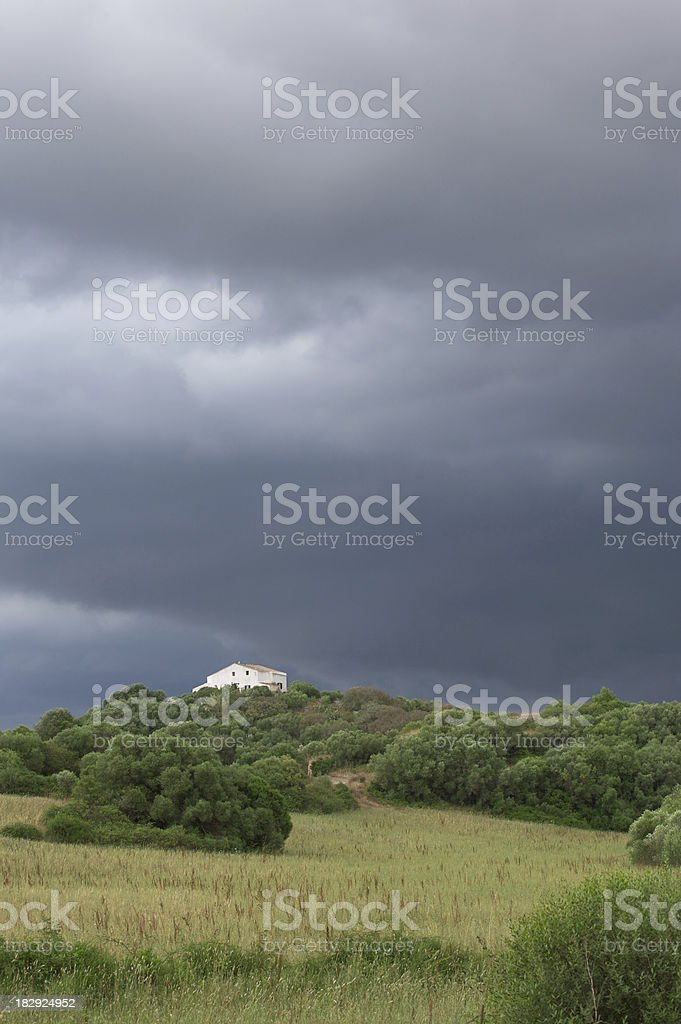 farmhouse under stormy skies stock photo