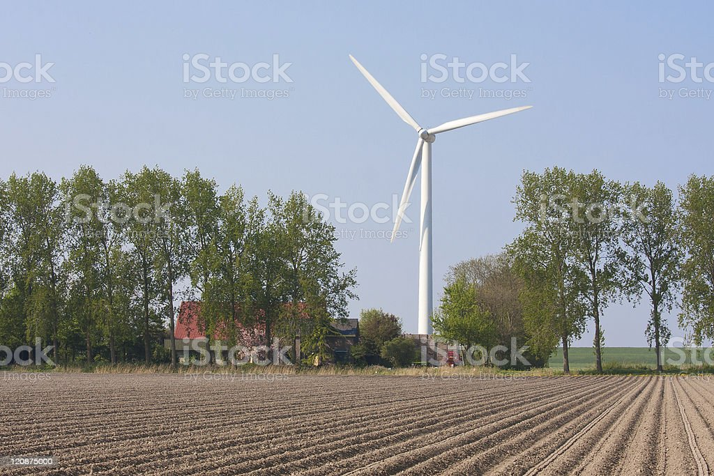 Farmhouse with a windturbine royalty-free stock photo