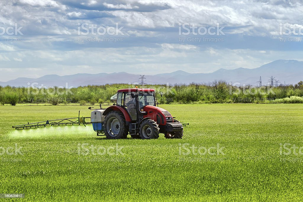 Farming tractor spraying on field royalty-free stock photo