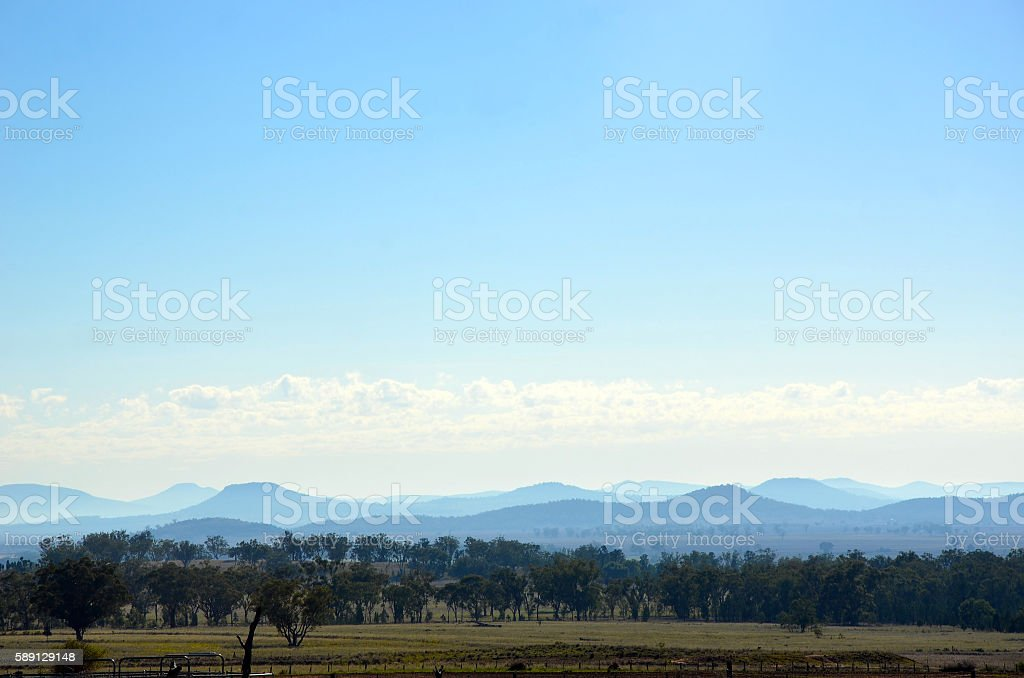 Farmland and forest landscape with misty mountains stock photo