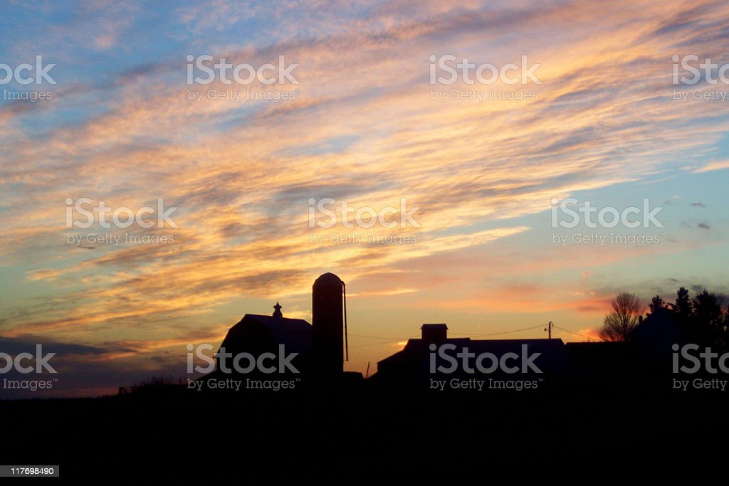 farmland sunset with farm buildings in silhouette stock photo