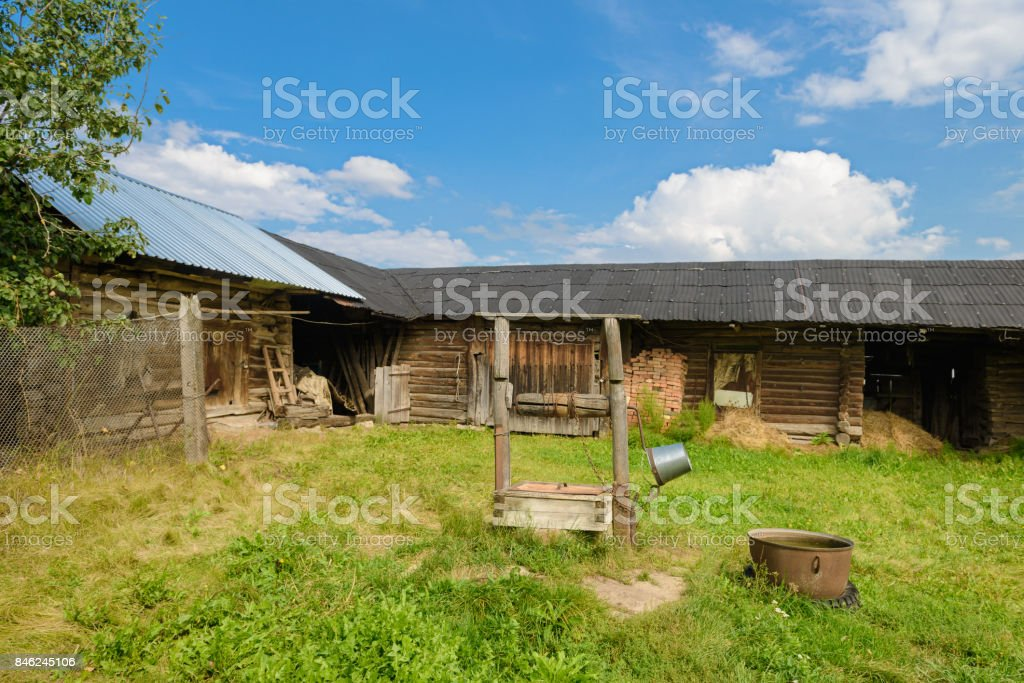 farmyard with a wooden barn and a well stock photo