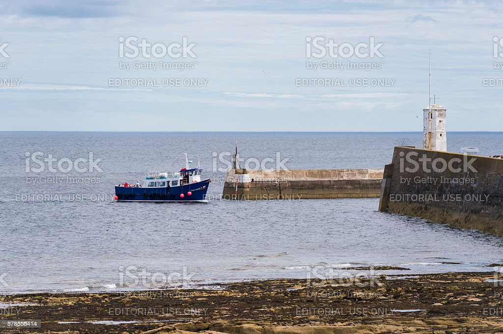 Farne Island excursion boat with passengers arriving at Seahouses harbour stock photo