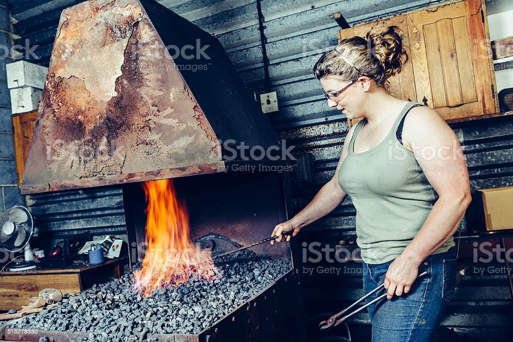 Farrier at her forge stock photo